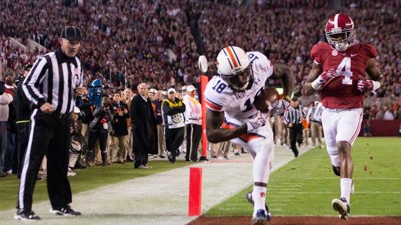 Alabama defensive back Eddie Jackson (4) looks on as Auburn wide receiver Sammie Coates (18) scores a touchdown during the Iron Bowl at Bryant-Denny Stadium in Tuscaloosa, Ala., on Saturday, Nov. 29, 2014.