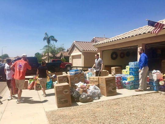 Donated supplies for victims of Hurricane Harvey stack up outside the home of Sean and Kim Saxon.