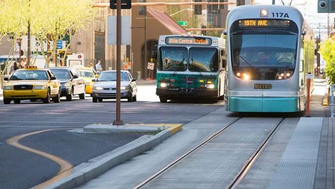 A city bus and Light Rail train at Van Buren St. and Central Ave. in Phoenix on Tuesday, March 10, 2015.
