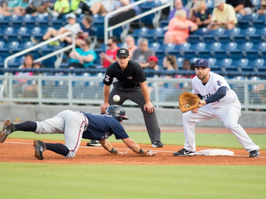 Dylan Moore (8) safely slides back into first base ahead of the throw to Eric Jagielo (7) during the Mississippi Braves vs Blue Wahoos baseball game in Pensacola on Tuesday, June 13, 2017.  However, pitcher Luis Castillo was called for a balk and Moore was awarded second base.