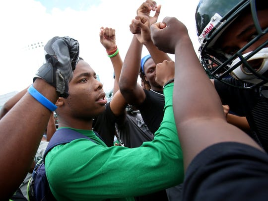 Cass Tech defensive back Kalon Gervin joins his teammates in a huddle before a light practice on the football field at Cass Technical High School in Detroit, Aug. 18, 2017.