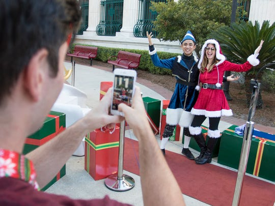 Josh Ward snaps a photo Friday, Nov. 24, 2017, of his wife, Rebekah, and one of Santa's helpers before the Elf Parade in downtown Pensacola.