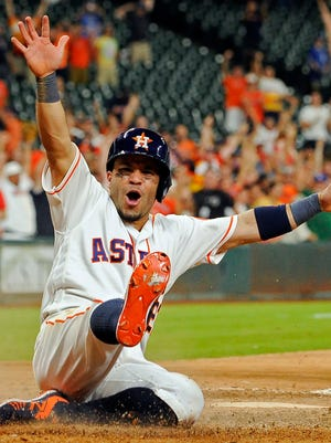 Houston Astros' Jose Altuve scores the winning run on Carlos Correa's single in the 14th inning of a baseball game against the Toronto Blue Jays, Monday, Aug. 1, 2016, in Houston. Houston won 2-1.