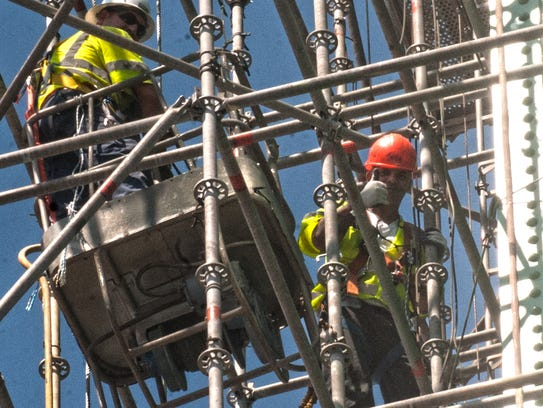 Painters work in baskets inside tower scaffolding on