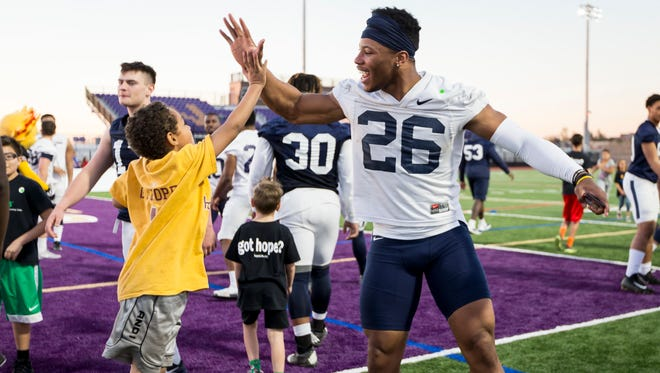 Steven Green, 9 of Glendale, Ariz., high-fives Penn State running back Saquon Barkley during a charity kickball event with the Children's Cancer Network and HopeKids on Wednesday, Dec. 27, 2017, in Scottsdale, Ariz. Penn State plays Washington in the Fiesta Bowl on Saturday. (Joe Hermitt/PennLive.com via AP)/PennLive.com via AP)