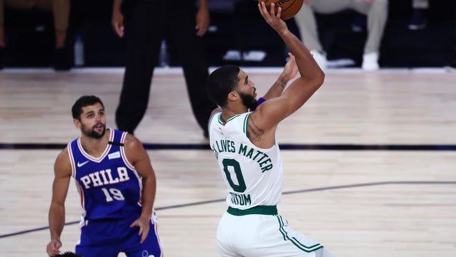 Boston Celtics forward Jayson Tatum (0) shoots past Philadelphia 76ers guard Raul Neto (19) during the second half of Game 4 of an NBA basketball first-round playoff series, Sunday, Aug. 23, 2020, in Lake Buena Vista, Fla.