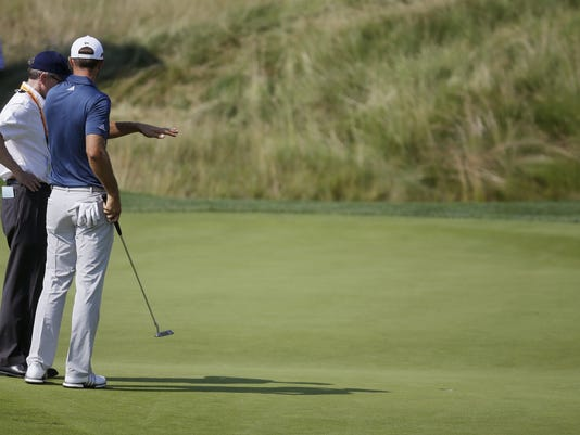 FILE - In this June 19, 2016, file photo, Dustin Johnson, right, talks to a rules official on the fifth green during the final round of the U.S. Open golf tournament at Oakmont Country Club in Oakmont, Pa. The USGA and R&A introduced a modern set of rules effective in 2017 designed to make them easier to understand. (AP Photo/John Minchillo, File)