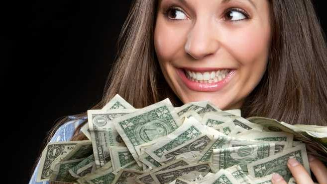 A woman smiling and holding a bundle of loose dollar bills in her arms.
