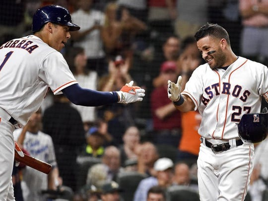 Eric Christian Smith/AP The Houston Astros' Jose Altuve, right, celebrates his solo home run off Oakland Athletics starting pitcher Chris Smith with Carlos Correa in the sixth inning of Monday's game in Houston.