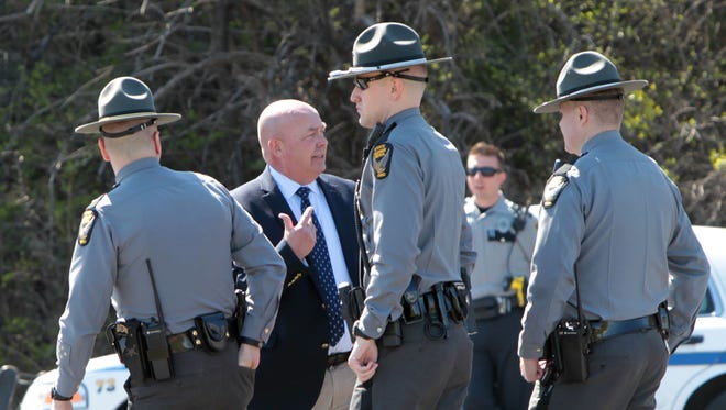 Major Mike Horton (second from left) of the Hamilton County Sheriff's Department, briefs three Ohio State Highway Patrol troopers after they arrived at the scene on southbound I-75, just south of Sharon Road.