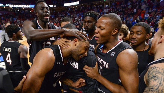 South Carolina guard Sindarius Thornwell (0) is mobbed by his teammates after the Gamecocks defeated Duke 88-81 in the 2nd round of the NCAA Tournament at Bon Secours Wellness Arena in downtown Greenville on Sunday, March 19, 2017.