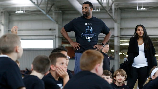 Former Lions star receiver Calvin Johnson and his wife, Brittney, look around at a group of kids attending his first annual Hard Count Athletics presents Megaton Camp at Ultimate Soccer Arenas in Pontiac on Saturday.