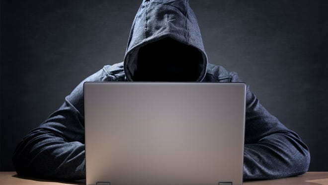 A person wearing a dark hood sits in front of a laptop.