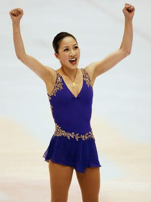 In a file photo from Feb. 19, 2002, Michelle Kwan raises her fists in triumph after completing her short program at the Salt Lake Winter Olympic Games.