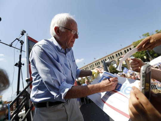 Democratic presidential candidate Bernie Sanders signs a campaign sign as he comes off The Des Moines Register Soapbox stage Saturday, Aug. 15, 2015, at the Iowa State Fair in Des Moines.