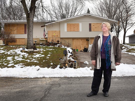 Patti Goke stands in front of a home along Longview