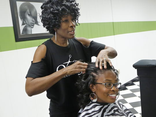 Debra Wilburn talks with Tenecia Waddell as she styles her hair October 10, at Onyx Styling & Braiding Salon, 20 N. Earl Ave. in Lafayette. Wilburn, who co-owns the salon, and Waddell, a patrol officer on the Purdue University Police Department, say the idea of people moving to the area from Chicago and bringing with them the crime of the big city is largely overblown.