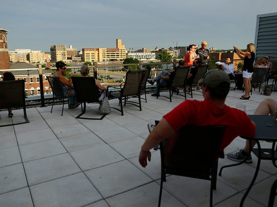 Patrons hang out on the new Roof Tap patio at Titletown Brewing Company's Tap Room in downtown Green Bay on Wednesday, July 13, 2016.
