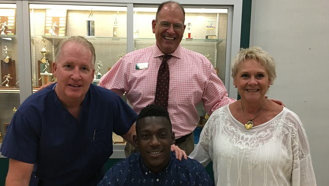 Fort Myers High kicker Josias Jean signs a football scholarship to Alcorn State University on Friday, June 2, 2017. Jean, who also will run track at the Mississippi university, is accompanied by, from left, Green Wave kicking coach Steve Lennon, Fort Myers Principal Dave LaRosa and Green Wave track coach Sheryl Jones.