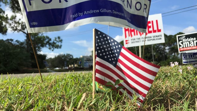 Voters drive by a gauntlet of campaign signs outside the Cummings Library in Palm City during the midterm election.