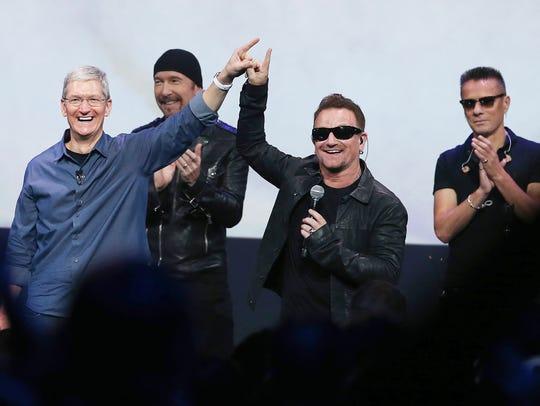 Apple CEO Tim Cook, left, and U2 singer Bono gesture