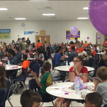 """Crowd at Thursday's Blue Angels Elementary Little Hero's Military Breakfast watch the projection screen while Jill Hernandez reads from her book, """"Home is Where the Navy Sends You: Naval Air Station Pensacola, Florida."""""""