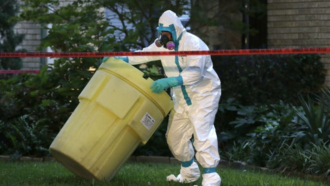 A hazmat worker moves a barrel while cleaning outside an apartment building of a hospital worker, on Oct. 12, in Dallas.