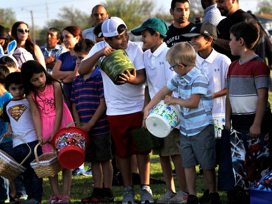 Children ready their buckets prior to Saturday's Evening Easter Egg Hunt at the Lee Sports Complex.
