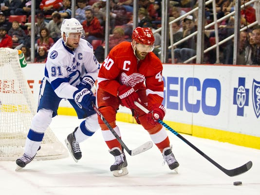 Tampa Bay Lightning forward Steven Stamkos (91) defends Detroit Red Wings forward Henrik Zetterberg (40), of Sweden, during the first period of an NHL hockey game in Detroit on Sunday, Nov. 9, 2014. (AP Photo/Tony Ding)