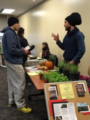 Kyle Ray, left, of Iowa City talks with Derek Roller of Mechanicsville-based Echollective CSA during the CSA Fair at the Iowa City Public Library on Sunday.