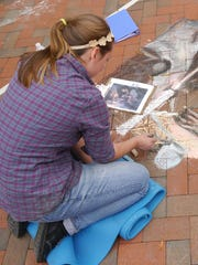 Sidewalk artist and JMU student Alycia East of Waynesboro at the Virginia Fall Foliage Festival Art Show in downtown Waynesboro Saturday, Oct. 10, 2015.