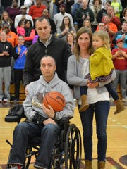 Shane Green, left, with his twin brother Shawn Green and Shawn's wife, Erin, and daughter, Avery, at a benefit game.