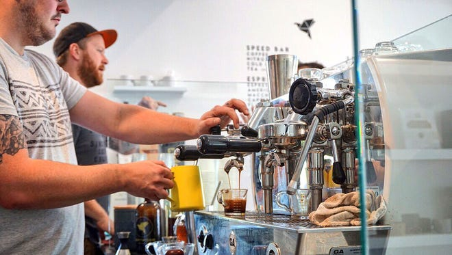 Driftwood Coffee Co. co-owners Luke Bentley (left) and Lance Linderman (right) serve coffee to customers on April 3, 2018.