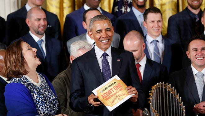 President Obama holds up a ticket for Wrigley Field presented to him by Cubs co-owner Laura Ricketts, left, during a ceremony in the East Room of the White House Monday.
