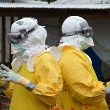 Medical workers wearing Personal Protective Equipment (PPE) gesture inside the high-risk area of the Elwa hospital runned by Medecins Sans Frontieres (Doctors without Borders), on September 7, 2014 in Monrovia.