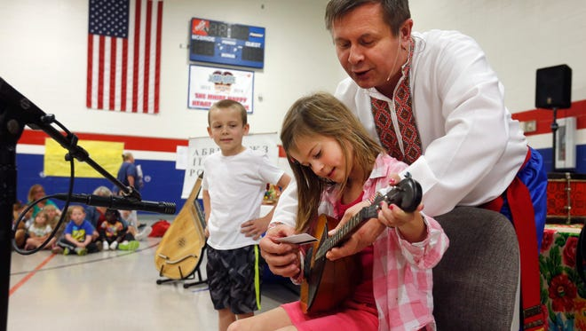 Sergei Shapoval shows Lauren Moseley how to play the domra on Monday, May 2, 2016 at McBride Elementary School during a Ukrainian Cultural Kaleidoscope assembly at the school.
