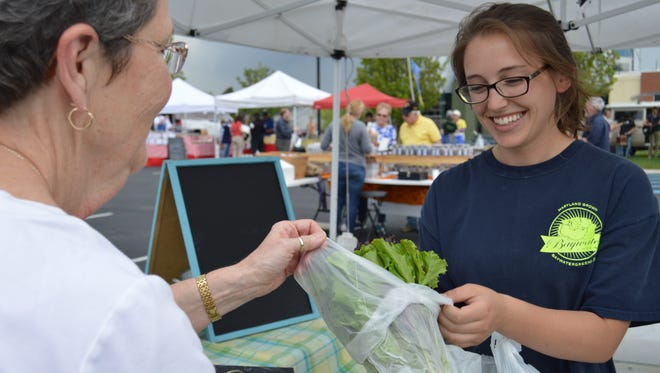 Jess Molnar, 22, sells fresh lettuce from Bay Water Greens at the Milton's Farmers' Market April 22.
