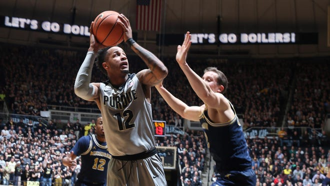 Purdue Boilermakers forward Vincent Edwards (12) takes a shot against Michigan Wolverines forward Duncan Robinson during the first half at Mackey Arena.