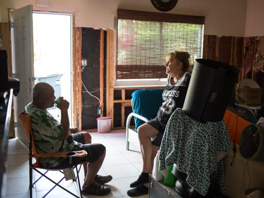 Rodney and Lori Malone sit together in the disheveled living area of their Bonita Springs home, which is still left with significant damage in the aftermath of Hurricane Irma, as seen on Friday, Dec. 8, 2017.