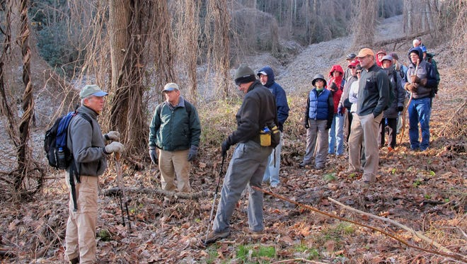 Hikers pause for a little history along Swannanoa Creek, once part of the main route between Old Fort and Asheville.