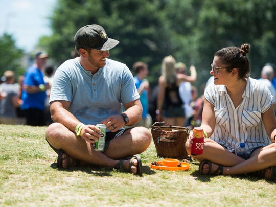 Corey and Kara Fitzpatrick of Knoxville sit on the grass at Big Kahuna Wing Festival in Worlds Fair Park Saturday, June 16, 2018.