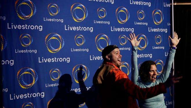 Guests pose with a new logo for Livestrong at an event in Austin, Texas, on Feb. 3. The cancer charity is on a mission to reinvent itself. It has survived a dramatic fall in contributions and donations since founder Lance Armstrong's performance-enhancing drug scandal.