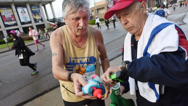 Ray Gildea, left, of Madison, adjusts his running gear a few miles into Saturday's Mississippi Blues Marathon with help from Thomas Kennedy of Columbus, a fellow marathoner acting as Gludea's support crew for the race.  The event marks the 150th marathon for the 63 year-old Gildea.