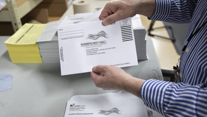 Absentee voting manager Matt Kelly holds the ballot envelopes that will be used to mail ballots at the Franklin County Board of Elections office in Columbus last month. Ohio's 88 county boards of elections are dealing with an unprecedented level of absentee ballot requests more than two months before Election Day.