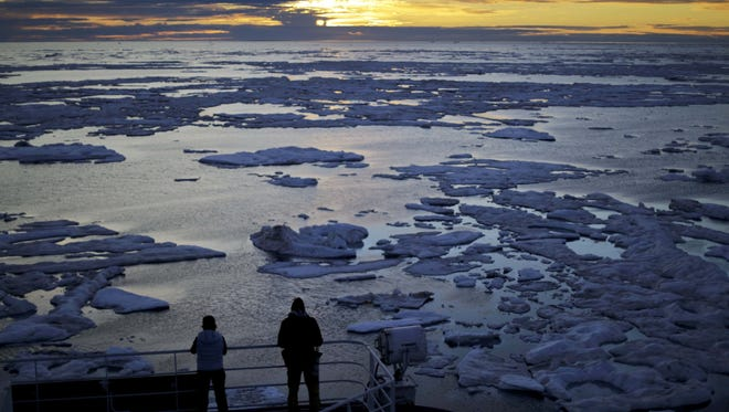 In this July 21, 2017 file photo, researchers look out from the Finnish icebreaker MSV Nordica as the sun sets over sea ice in the Victoria Strait along the Northwest Passage in the Canadian Arctic Archipelago. Studies show the Arctic is heating up twice as fast as the rest of the planet. Scientists are concerned because impacts of a warming Arctic may be felt elsewhere.