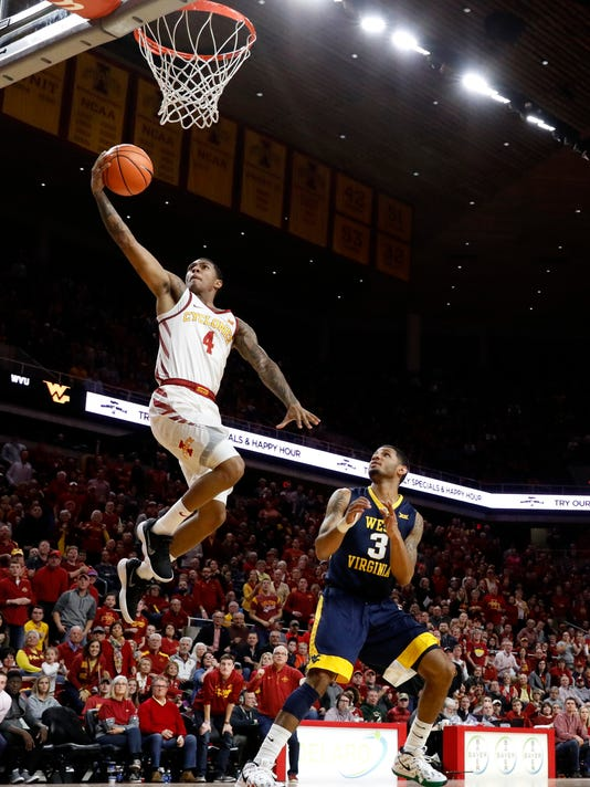 Iowa State guard Donovan Jackson (4) drives to the basket over West Virginia guard James Bolden (3) during the second half of an NCAA college basketball game Wednesday, Jan. 31, 2018, in Ames, Iowa. Jackson scored 25 points as Iowa State won 93-77. (AP Photo/Charlie Neibergall)
