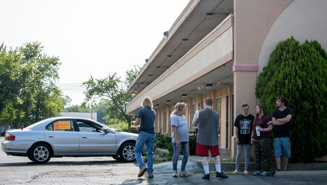 In mid-August, residents talk outside the Red Carpet Inn on South Madison Street about the city's plan to shut the motel down.