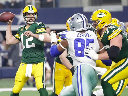 Green Bay Packers quarterback Aaron Rodgers (12) throws under pressure as tackle Bryan Bulaga (75) blocks against the Dallas Cowboys at AT&T Stadium in Arlington, TX Sunday, January 15, 2017.