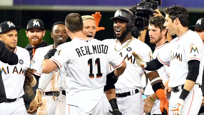 Miami Marlins catcher J.T. Realmuto (11) celebrates his game winning RBI double with teammates during the inning inning against the New York Mets at Marlins Park. The Marlins won 3-2.