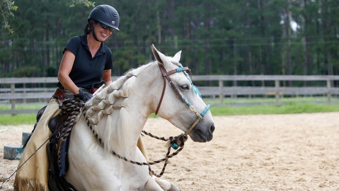 Horse trainer Marsha Hartford-Sapp works with Chason Dreams, the horse that won her this year's Extreme Mustang Makeover,  at her stables off Highway 90 East June 12.